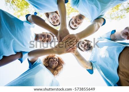 Group of volunteer forming huddles in park