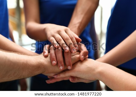 Group of volunteers joining hands together, closeup