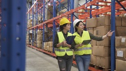 group of warehouse asian chinese female staff discussing work with tablet and clipboard and walking in large stockroom.