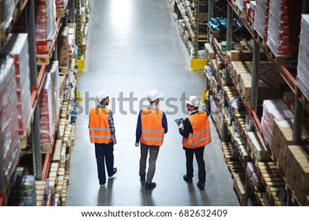 Group of warehouse workers wearing hardhats and reflective jackets waking in aisle between tall racks with packed goods, back view #682632409