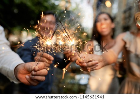 Group of wedding guests burning Bengal lights outdoors at cocktail party #1145631941