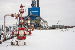 Group of wellhead and reinforcement valves on the rig land background in winter. Oil, gas industry. Russia.