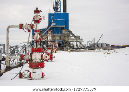 Group of wellhead and reinforcement valves on the rig land background in winter. Oil, gas industry. Russia. stock photo