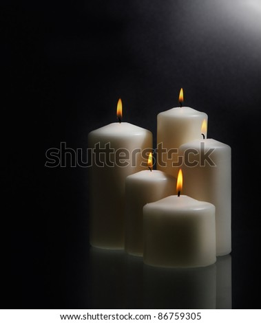 Group of white burning candles over black background