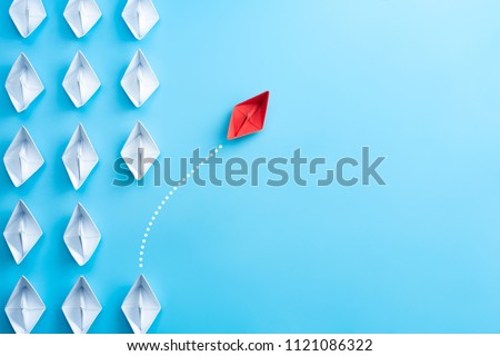 Photo of  Group of white paper ship in one direction and one red paper ship pointing in different way on blue background. Business for innovative solution concept.