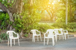Group of white plastic chairs in green park with light flare.