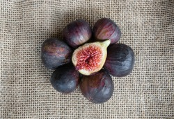 Group of whole figs in circle and one slice in the middle, sackcloth background, copy space, horizontal