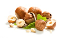 Group of whole, half and small pieces hazelnuts on white background. Isolated