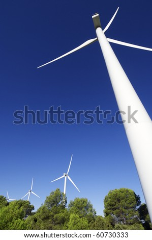 group of wind turbines in a wooded area