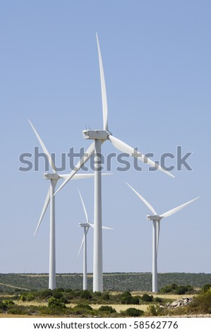 group of windmills for electric power production on a clear day