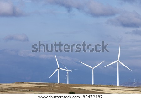 group of windmills for electricity production with stormy sky