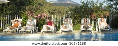 group of woman in deckchairs around the swimming pool
