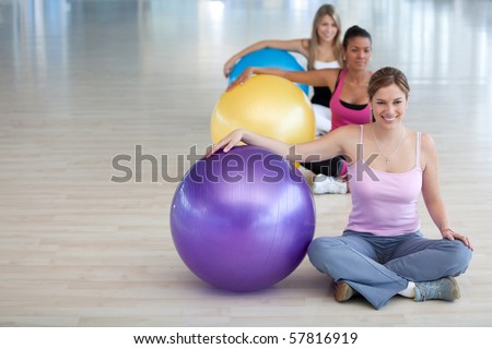 Group of women at the gym smiling with a pilates ball