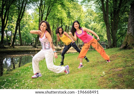group of women dancing a fitness dance or aerobics in an old park