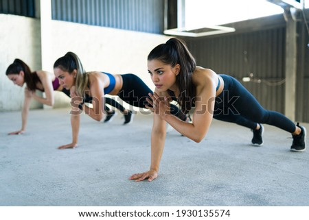 Group of women doing shoulder taps during a high-intensity interval training at the gym. Three fit caucasian women working out with a cardio routine indoors  Photo stock ©