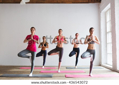 Group of women doing yoga in a fitness gym.