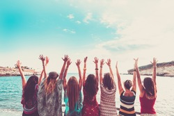 group of women enjoying and celebrate summer vacation all together saying hallo to the ocean and the nature. young people leisure activity, all hands up and vintage colors style. fashion dresses