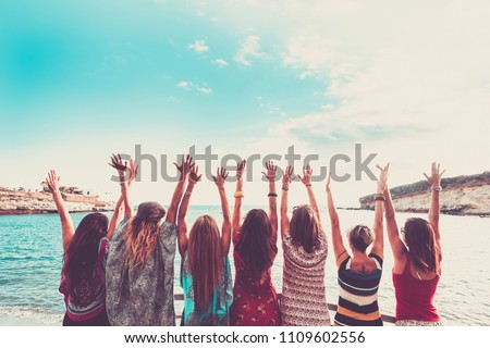 group of women enjoying and celebrate summer vacation all together saying hallo to the ocean and the nature. young people leisure activity, all hands up and vintage colors style. fashion dresses  #1109602556