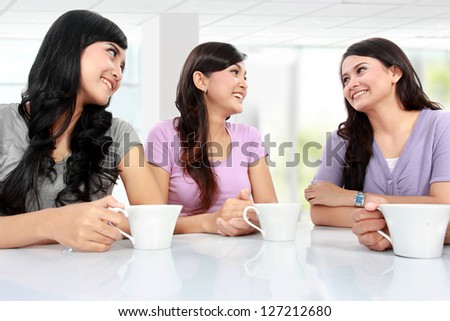 group of women friends chatting over coffee at home