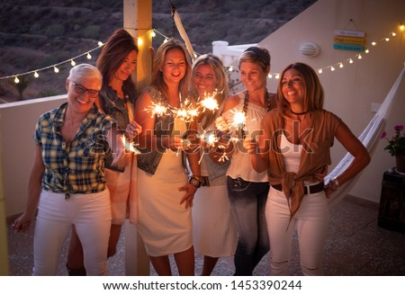 Group of women friends enjoying the dusk and the party on the terrace with sparkling. Happiness together and beautiful people