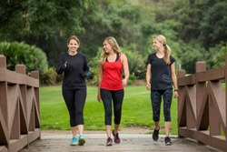 Group of women in their 30s walking together in the outdoors. Cute blond and fit women in their mid 30s who are active and working to stay healthy. Full length photo with copy space
