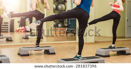 Group of women making step aerobics in fitness club - view from the backside