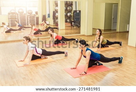 Group of women making step aerobics in the fitness class