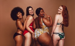 Group of women of different race, figure and size in swimsuits standing together and laughing against grey background. Diverse women in bikinis looking at camera.