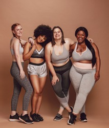 Group of women of different race, figure type and size in sportswear standing together over brown background. Diverse women in sports clothing looking at camera and laughing.
