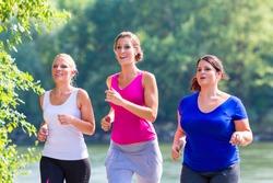 Group of women running at lakeside jogging