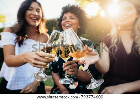Group of women sitting outdoors and toasting champagne. Close up of female having drinks at party outdoors.