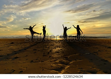 Group of women standing on the beach with the shadow morning backlight, silhouette image.