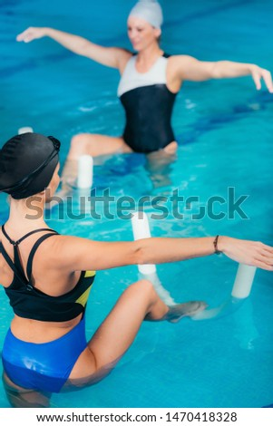 Group of Women with Female Instructor, Water Aerobics Class.