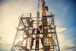 group of worker in safety uniform install reinforced steel column in construction site during sunset time