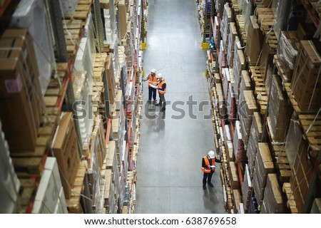 Group of workers in aisle between shelves with packed goods