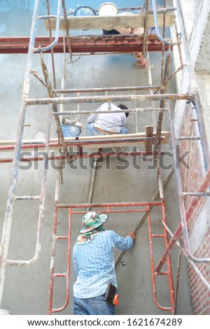 Group of workers stand on the steel scaffolding and builds plastered cement wall in the house under construction