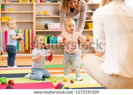 Group of workers with babies in nursery or kindergarten ストックフォト ©