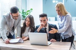 Group of worried and disappointed business people working in office and analyzing bad results from paperwork and laptop during office meeting