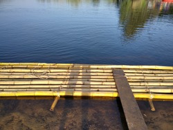 Group of yellow bamboo floating at lakeside for get on boat