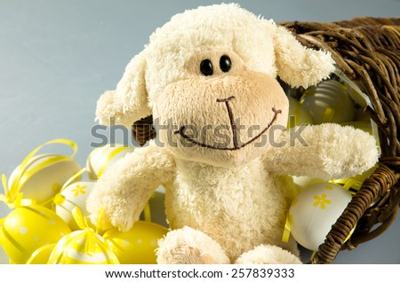 group of yellow easter eggs in wooden basket and white sheep #257839333