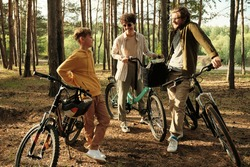 Group of young active cheerful people standing by their bicycles on the ground among trunks and riverside and chatting in the country