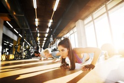 Group of young active fitness people doing push ups together in the sunny gym.