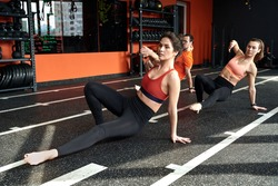 Group of young adult athletic people training in animal flow style, making kick to the side, spending workout session together with personal coach in gym club