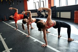 Group of young adult sporty people training together in fitness center, working out at animal flow style, making crab position