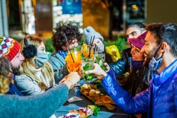 group of young adults celebrating christmas holidays toasting together in a party at night after coronavirus lockdown reopening.happy friends wearing protective face mask in open bar restaurant.