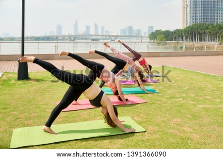 Group of young adults exercising on exercise mat and doing stretching exercises on yoga class outside