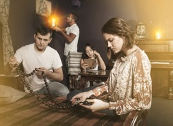 Group of young adults inspecting wooden rosary, trying to find solution of conundrum in escape room with antique furnitures