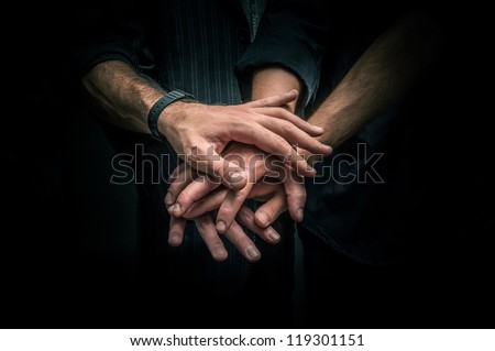 Group of young adults making a pile of hands against dark background