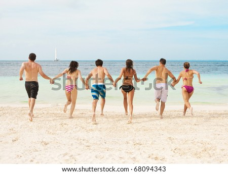 Group of young adults running together on the beach