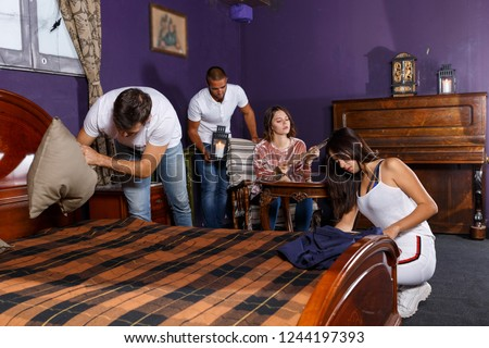 Group of young adults trying to find solution of quest in escape room with antique furnitures